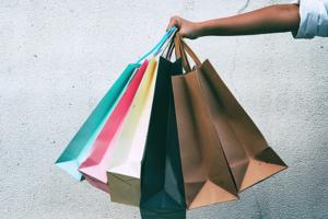 Damenhand hält 6 Stück Einkaufstaschen vor Betonmauer