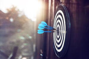Fokus Recherche: Dartpfeil im Bullseye einer Dartscheibe