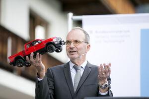 Burkhard Schlechter hält ein Modellauto in die Luft.