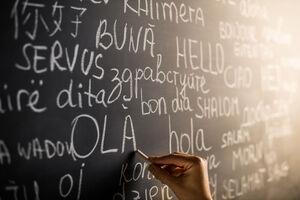 Hand schreibt mit Kreide das Wort Hallo in verschiedenen Sprachen