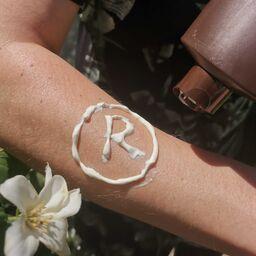 Registered-Symbol mit Sonnencreme auf Arm gezeichnet