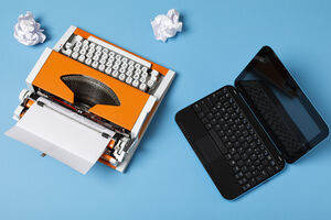 an orange typewriter with crumpled paper and a computer, photo taken from above
