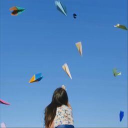 Frau wirft Papierflieger in die Luft
