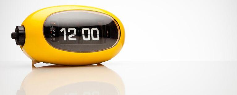 Gelber retro-wecker zeigt 12 Uhr an.