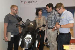 am Bild die Präsidentin des Österreichischen Patentamtes mit Teilnehmern des Innovationsmarathons in Alpbach rund um ein modernes Motorrad
