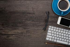 Schreibtisch mit Kaffeetasse, Brille, Handy und Tastatur