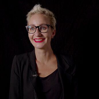 Portrait von Miriam Unterlass vor schwarzem Hintergrund