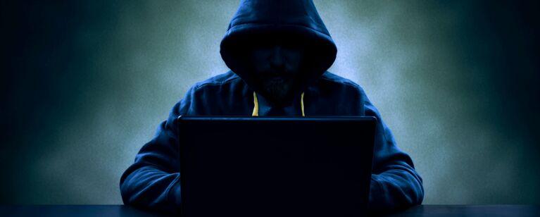 Mann mit dunkler Kleidung sitzt vor Computer.