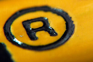 Zeichen für registrierte Marke (Buchstabe R in einem Kreis) auf gelbem Hintergrund