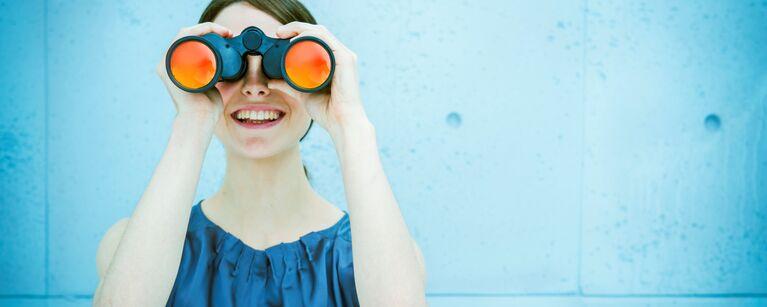 Frau steht vor einer blauen Wand und schaut durch ein Fernglas